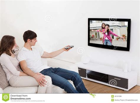 couch online tv couple in livingroom watching television stock photo