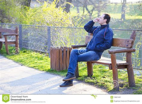 sitting in a park bench man sitting on a park bench stock image image 13821451