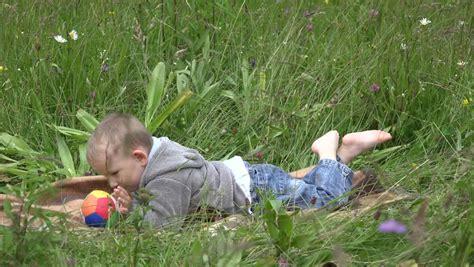 little girl lying on green grass in the park stock