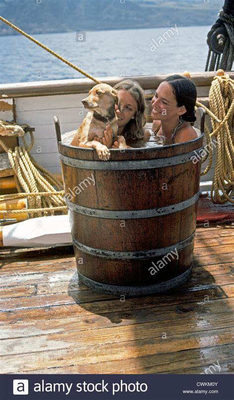 two dogs in a bathtub rub a dub dub two girls and a dog in a tub take a bath in a wooden stock photo