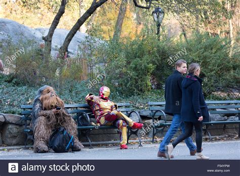 buy a bench in central park movie characters in costume chilling out on park bench as couple walk stock photo