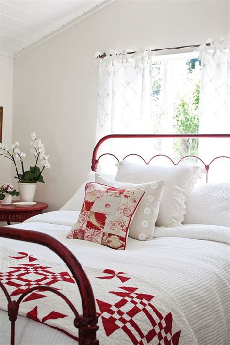red and white bedroom white bedroom with red metal bed frame and quilt at the