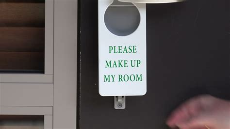 make my room woman hangs please make up my room sign on hotel or motel