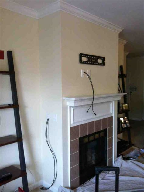 tv mounting a fireplace with wires concealed in the