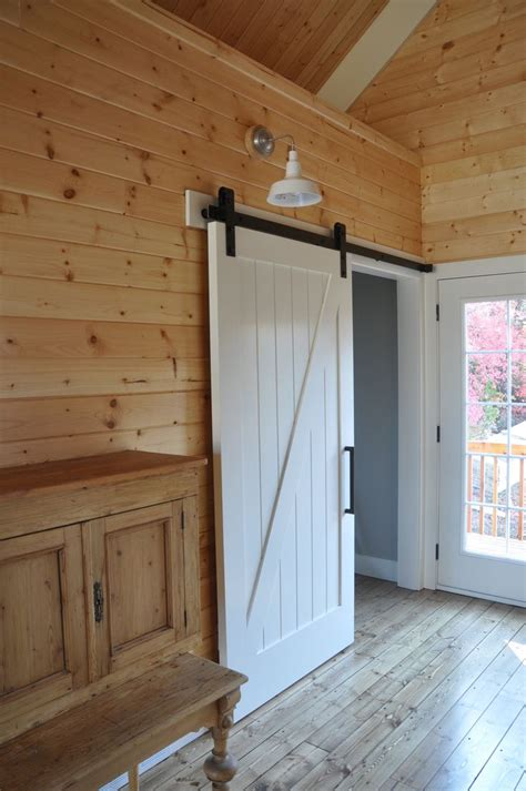 Light Barn Doors Farmhouse Barn Door Painted White With Black Hardware Looks Great With The Wood Paneling On The