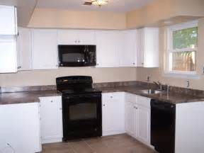 Kitchen With White Cabinets And Black Appliances Black And White Kitchen Cabinets