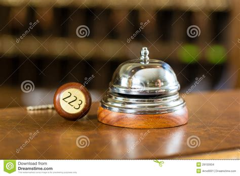 reception hotel bell and key lying on the desk stock