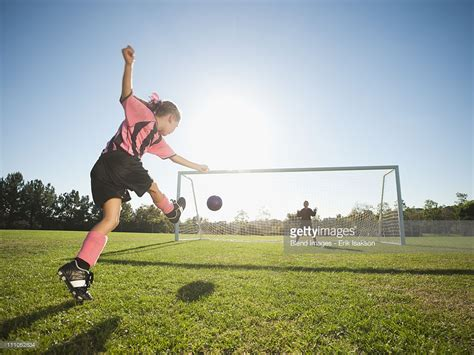 soccer player kicking soccer at net stock photo