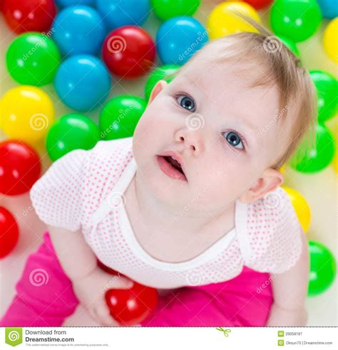 colorful baby baby among colorful balls royalty free