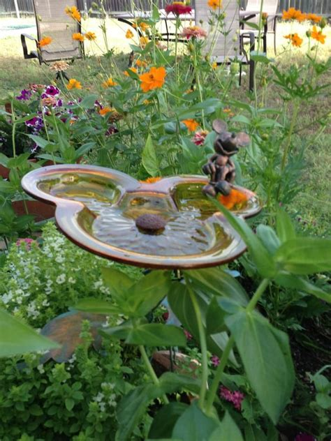 mickey mouse birdbath in garden i want this in my flower