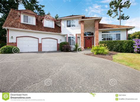 white house garage american large white house with two garage dors red door and brick columns stock
