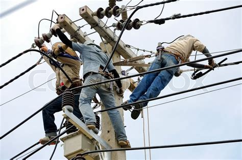 Wire Teamwork team work electrician on electric poles stock photo