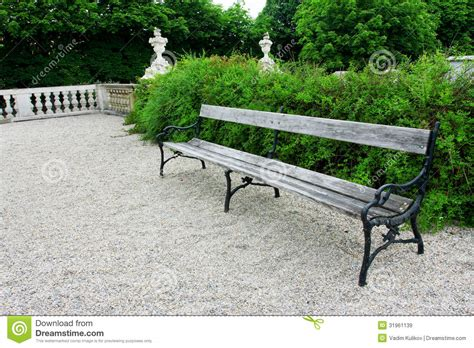 green park bench wooden bench in a green park with shrubs royalty free