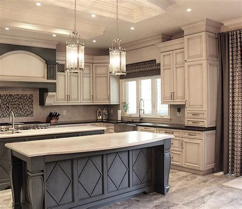 antiqued white kitchen cabinets dark grey island with white countertop and antique white
