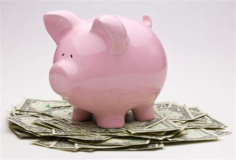 c a money bank pink piggy bank on top of a pile of one dollar bills flickr