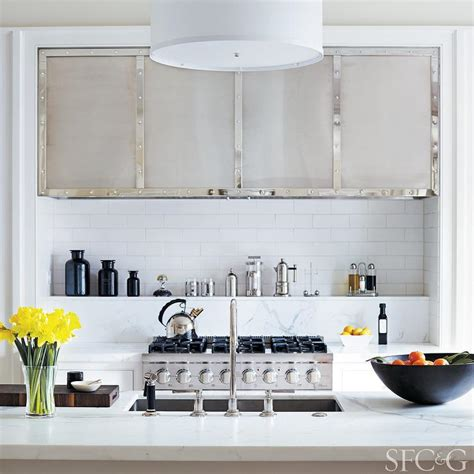 small white kitchen with steel hood cooktop spice shelf transitional kitchen
