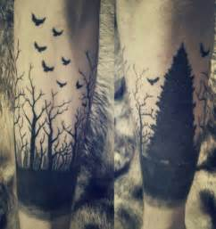 Small black flying birds and dark shaded forest tree tattoo
