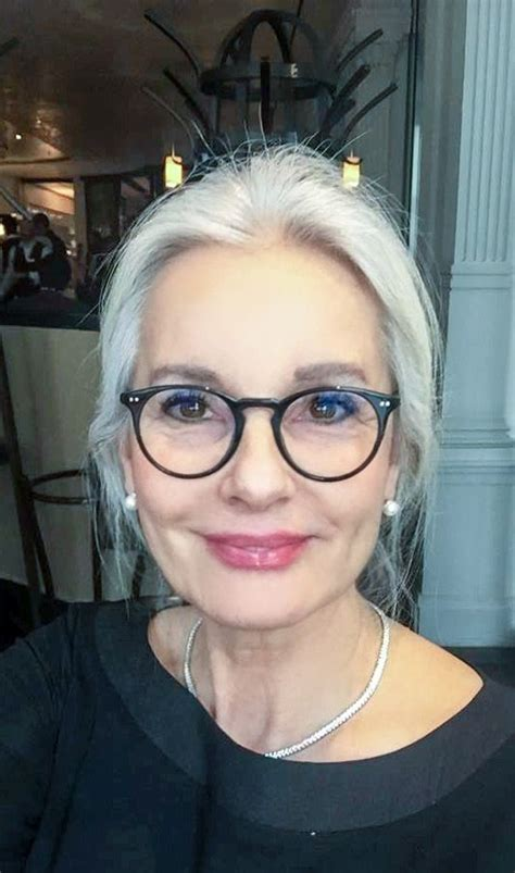 short salt and pepper hair white hair ponytail with black glasses black top