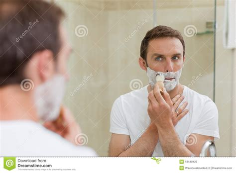 men in the bathroom man shaving in the bathroom royalty free stock photo