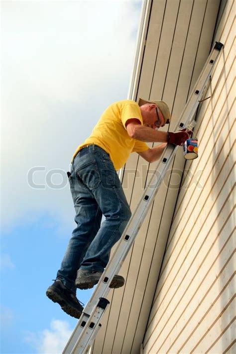 senior house painter climbing   ladder stock photo