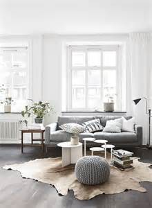 living room white walls white window frames light grey sofa timber floorboards grey