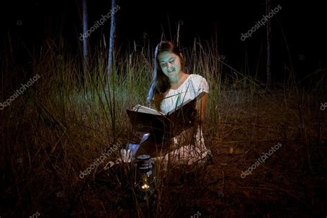 Young Woman Reading Magic Book At Dark Night Forest
