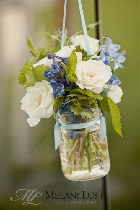 White roses and delphinium in hanging mason jar