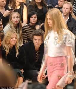 cara delevingne poses with harry styles backstage in a