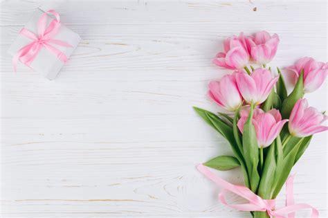 tulipanes rosados  regalo en  fondo de madera blanco