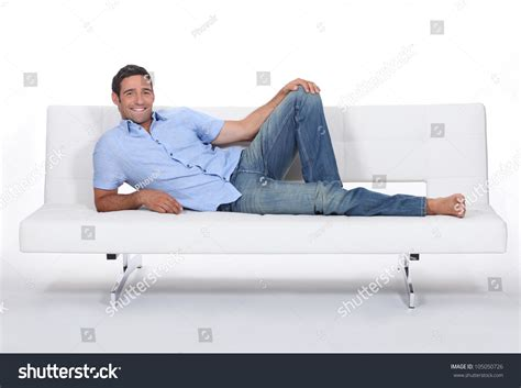 a man and a couch barefoot man lying on couch stock photo 105050726
