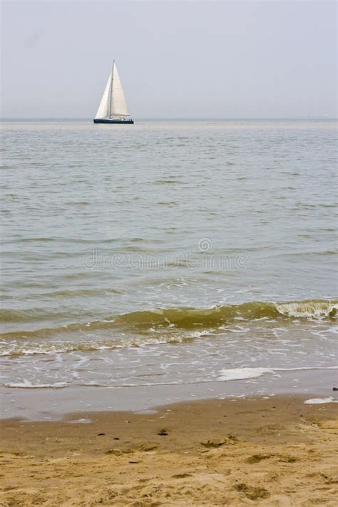 distances by boat sunny beach with sailing boat in distance stock photos