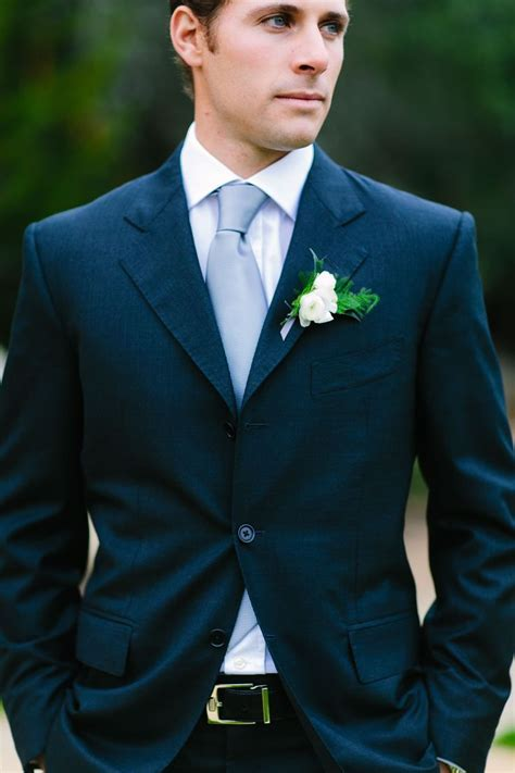 Groom: navy blue suit, rose and fern boutonniere   Rustic