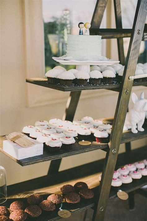 Shelf Of Cupcakes by Display Desserts On Shelves Supported By A Ladder Photo