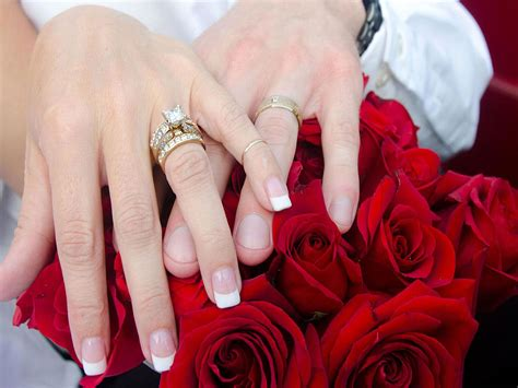 wedding holding hands hands fingers rings bouquet flowers