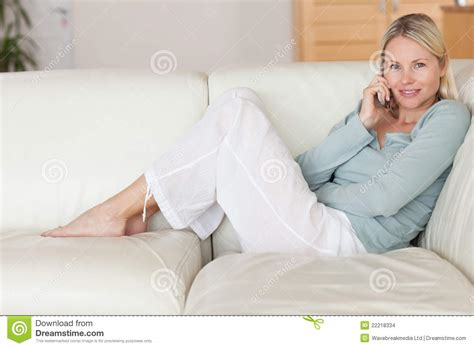 sitting on the couch woman sitting on the couch listening to caller stock
