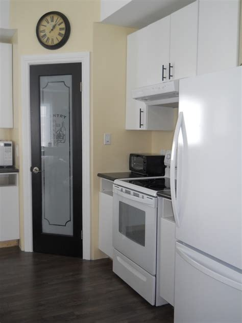 black pantry door with frosted glass white cabinets