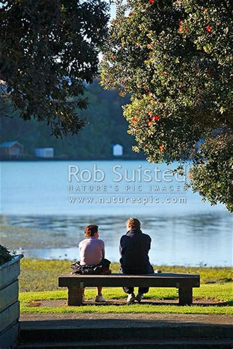 two people sitting on a bench two people sitting contemplating and talking on a park