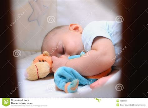 baby sleeping in his crib stock photo image 45398069