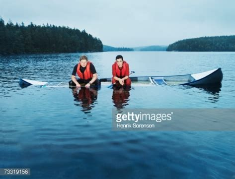 ship license mediah rowboat man and woman sitting in sinking canoe stock photo getty