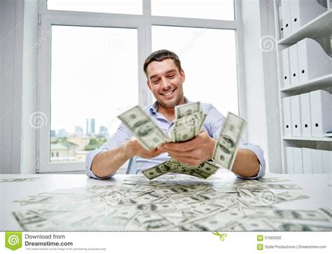 happy businessman with heap of money in office stock photo
