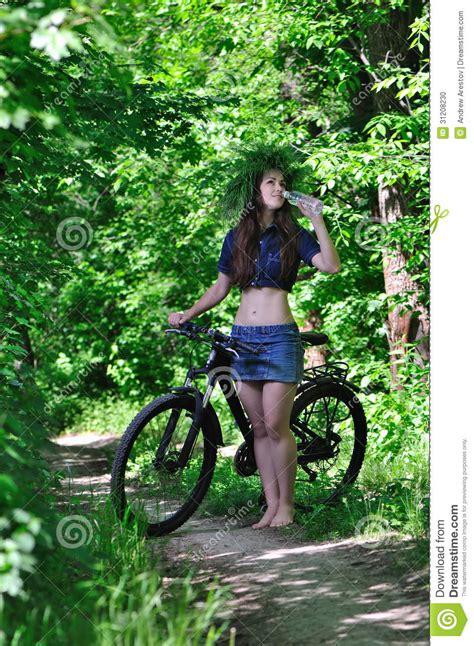 0008288607 the girl in the woods the girl in the woods on a bike drinking water stock photo