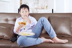fat kid on couch child boy kid fat burger diet eating cheeseburger stock