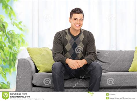 man couch man posing seated on a sofa at home stock image image