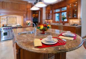 Rich patterned marble countertop extends to round dining space on this
