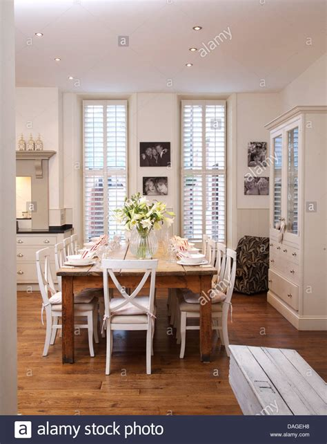 White Kitchen And Dining Room by White Chairs At Simple Wood Table In Modern White Kitchen