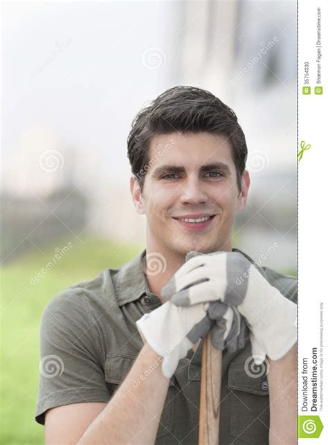 mens haircuts garden city portrait of young smiling man holding a rake on a roof top