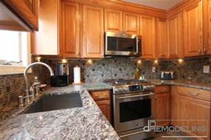 oak cabinets with glass mosaic backsplash