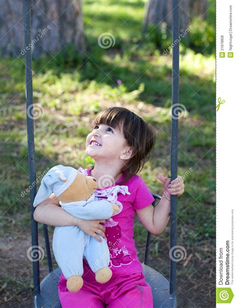 girl in swing smiling girl on a swing stock photo image of cute park
