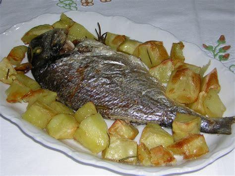 spigola al forno su letto di patate filetti di branzino con patate al forno in cucina con
