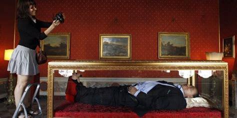 une statue de berlusconi sur un lit de mort en pantoufles